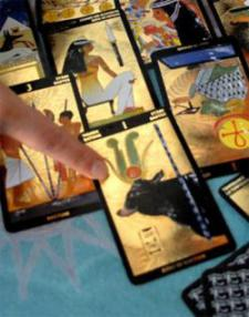 Emma reading Tarot cards from her guilded Egyptian tarot deck.